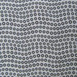 Small black circles on white fabric